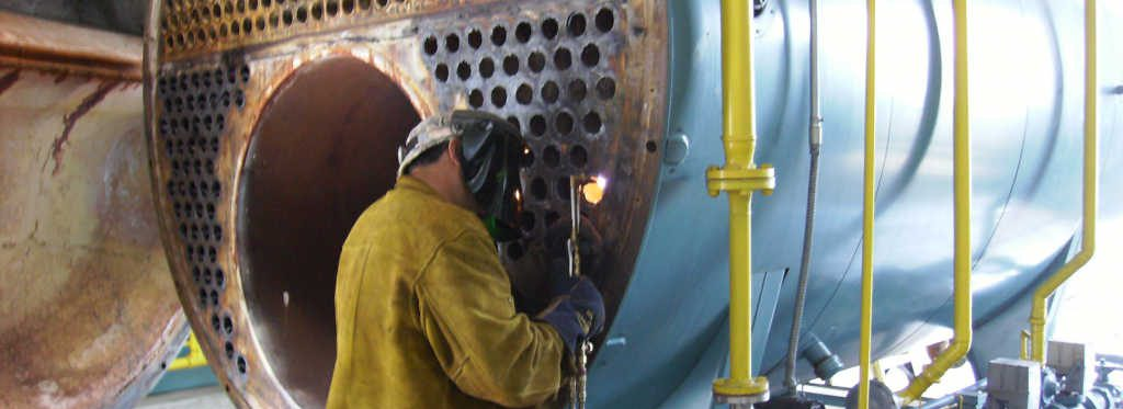 Welder working on a large commercial boiler system